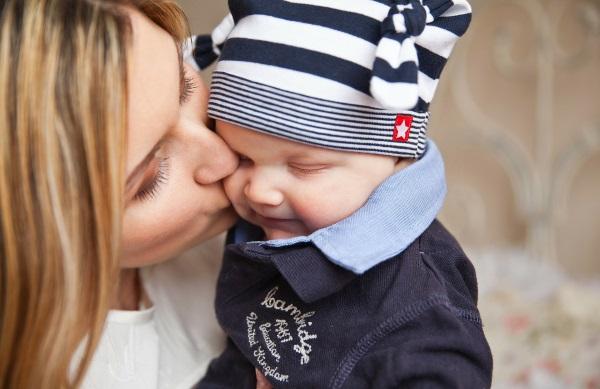 Eine Mutter küsst ihr Baby und kann dadurch Herpes übertragen