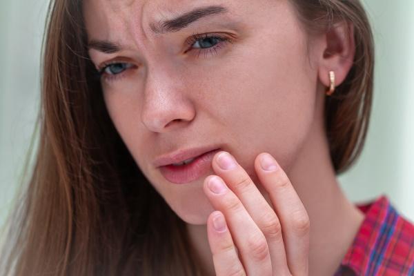 Frau mit gequältem Gesichtsausdruck - Herpes Menstrualis